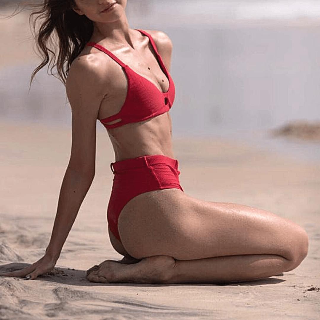 top escort model in red bikini on the beach